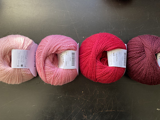 Four balls of yarn lined up in a row, left-to-right: light pink, pink, red, burgundy.