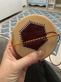 Hand holding a small wooden pin loom, with a mostly complete dark red woven hexagon.