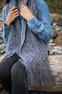 [Image Description: Someone wearing a bulky-weight cable-knit scarf. The scarf hangs over their shoulders and one end rests on their lap, with fringe spilling over their leg.]