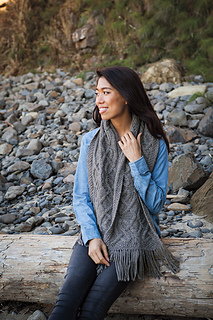 [Image Description: A woman sitting on a log, wearing a wide cabled scarf draped over her shoulders.  The scarf comes down to just above her lap, and has fringe on the ends.]