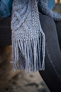 [Image Description: The fringed end of a knit scarf hanging down. There is a celtic-knot cable pattern visible on the end of the scarf.]