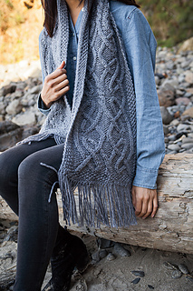 [Image Description: a bulky-knit cabled scarf hanging over someone's shoulder. The scarf has an intricate celtic-knot style cable across it.]
