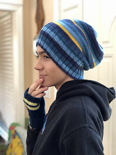 A teen boy looking left and holding his hand to his chin. He's wearing a blue hoodie and a blue and yellow striped slouchy hat.