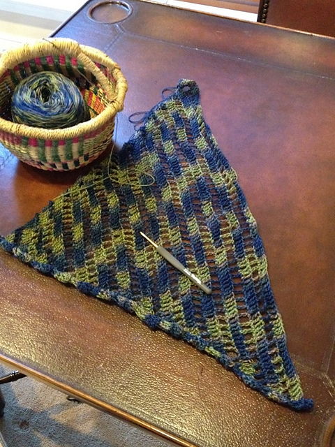 An in-progress crochet project in blue and green with diagonal rows of