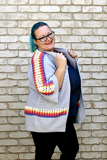 Curvy female with blue hair wearing a grey cardigan with accent purple, pink, orange, yellow and white puff stitches.