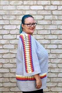 Side profile of curvy female with blue hair wearing a grey cardigan with accent purple, pink, orange, yellow and white puff stitches.