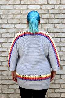 Back of curvy female with blue hair wearing a grey cardigan with accent purple, pink, orange, yellow and white puff stitches.