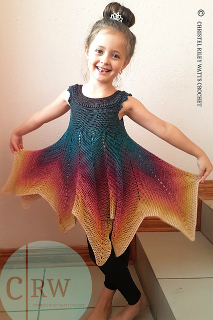 A little girl on a tiled staircase wearing a crocheted tank-style dress with a deeply pointed handkerchief hem. She has a big smile on her face and is holding out the skirt as if ready to twirl