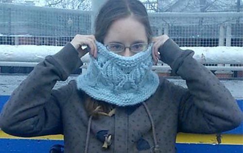 [Image Description: A woman holding a bulky-weight knitted cowl over her nose and mouth. The cowl has a lace and cable pattern.]