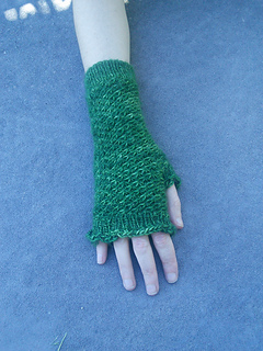 [Image Description: A knitted green fingerless mitten being modeled on someone's hand. The mitten's body is a textured spiral stitch, the cuff, thumb and top of the hand are ribbed.]