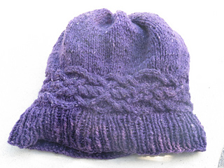 [Image Description: A purple worsted-weight knit hat laying flat. The hat has a ribbed brim, and a stockinette main body. Just above the ribbing, there is a celtic-knot style cable band that is knit horizontally. The top of the hat is gathered in slightly. ]