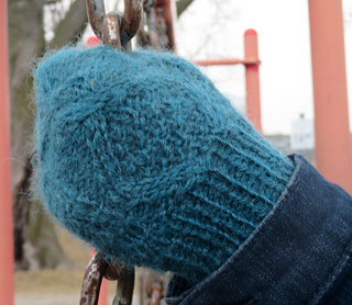 [Image Description: Someone wearing a cabled mitten and gripping a chain.  The mitten cables enclose a section of double moss stitch.]