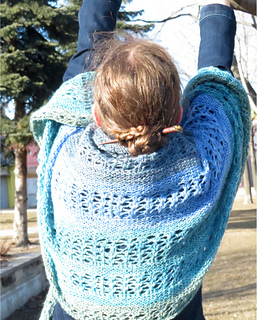 [Image Description: A woman with her back to the camera.  There is a crescent shawl done in garter stitch and lace draped across her back and arms.]