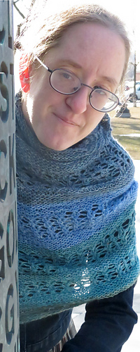 [Image Description: A woman wearing a shawl wrapped around her neck and shoulders.  The shawl is a crescent shawl with alternating stripes of garter stitch and lace, knit in a blue-to-green gradient.]