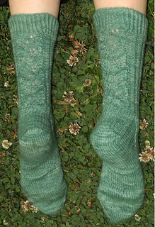 [Image Description: The back of a green lace sock.  The sock has lace around the leg, and a slipped stitch heel flap.]