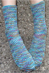 [Image Description: Someone wearing a pair of ribbed lace socks. The socks are blue with flecks of white, pink, and yellow. ]