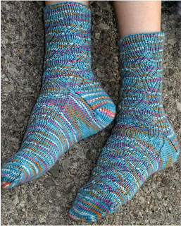[Image Description: Someone wearing a pair of ribbed lace socks. The socks are knit in fingering-weight.  The yarn is blue, flecked with white, pink, and orange. ]
