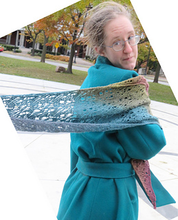 [Image Description: A woman with a gradient sock yarn shawl over one shoulder.  The end is caught in the wind and behind her.