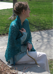 [Image Description: A woman wearing a large blue-green lace shawl.  She is holding the shawl at her neck with one hand.]