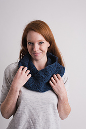 [Image Description: A woman with a dark blue worsted weight cowl looped once loosely about her neck.]