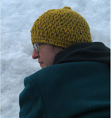 [Image Description: A woman wearing a crochet hat done in the textured alpine stitch]