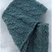 [Image Description: a cowl knit in light-blue worsted weight yarn, with a cable that crosses columns of knit stitches.]