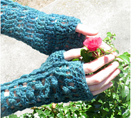 [Image Description: A person wearing a pair of fingerless crochet mittens. They have their hands around a small flower.]