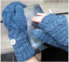 [Image Description: A person wearing a pair of flip-top convertible mittens.  They are working a touch screen with the exposed fingers of the right hand, the mitten top is buttoned back. ]