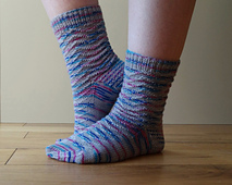 Side view of socks.  One foot is on tip tops and the other is flat on the floor. The sock has a wavy textured pattern