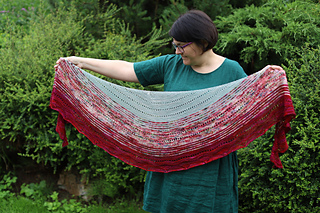 A woman with short brown hair holding a crescent shaped shawl in front of her knit in blue, speckle- red and red with vegetation in the background.