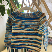 Completed baby sweater knit with variegated blue, brown, and white yarn. It has stripes of varying widths, and garter stitch panels on the outside of both arms. It is hanging from an umbrella swift, with a plant in the background.
