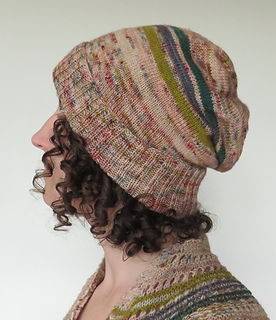 Brunette woman with curly hair wearing a pink, slouchy knit hat with a few stripes - white background.