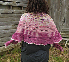 A woman with brown, curly hair facing away from the camera wearing a crescent shaped shawl over her shoulders knit with three shades of pink and a barn in the background.