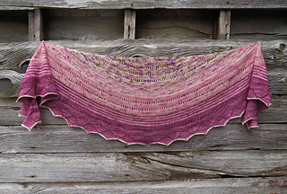 A long shot of a crescent-shaped shawl in three shades of pink speckled yarn with a barn wall in background.