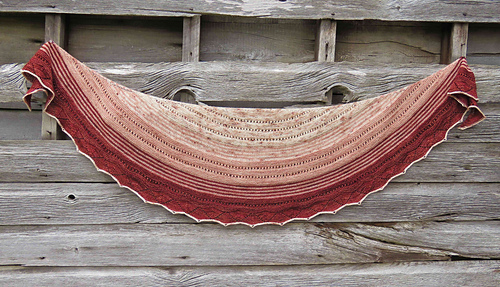 A crescent-shaped shawl in speckled yarn and three colours (beige, peach and red) with a barn wall in background.