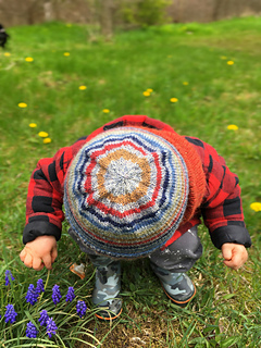 Toddler boy looking at the grass and wearing a striped knit hat showing the circles on the crown.