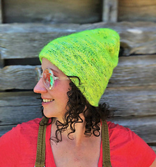 """A woman with brown, curly hair grinning looking left and wearing a neon yellow-green hat sitting """"tall"""" with a barn in a background."""