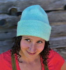 A woman with brown, curly hair wearing a mint coloured hat with a double-thick brim folded up and a barn in the background.