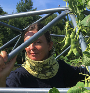a brunette woman standing in a geodesic dome with beans growing on it and wearing a cowl