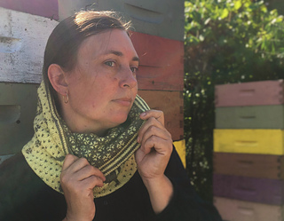 a brunette woman standing in front of colourful bee boxes wearing a cowl and pulling it down to make the lining visible