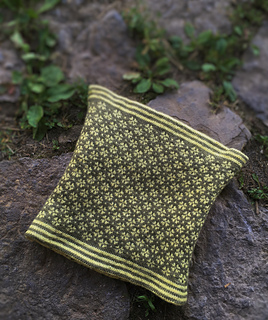 a yellow cowl with a patterned flower lining sitting on cobblestones