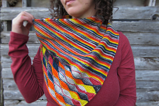 Woman in a red shirt with a multi-coloured kerchief-cowl and a barn in the background.