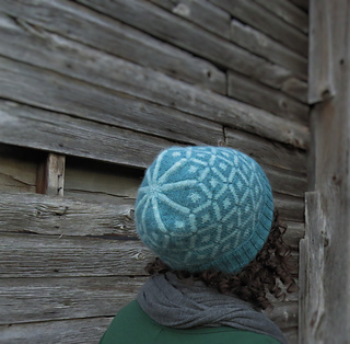 View of a woman with curly hair looking to the right with a barn in the background and wearing a blue hat with a diamond pattern.