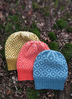 Three hats (blue, orange and yellow) with two different diamond patterns on a mossy background.