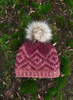 A two-tone pink chunky hat with a bold, diamond pattern and a fluffy, light brown, faux fur pom pom lying flat on a bed of moss.