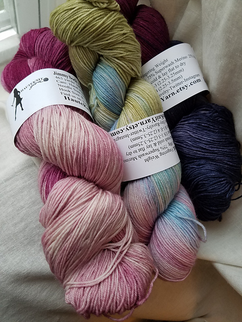 Three skeins of yarn; one is  purple / pink, one is pink / light blue / light green, and one is purple / dark blue