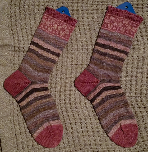 A pair of striped socks in red / beige / brown, with colorwork flowers at the cuffs