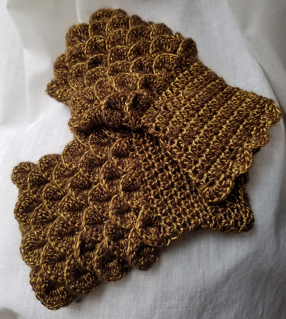 Fingerless gloves crochet in a bronze-colored yarn to resemble scale mail gauntlets