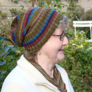 An older woman with short hair, glasses and a white jacket wearing a green striped slouch hat with a wide ribbed brim folded up.
