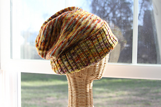 Speckled slouchy hat with a ribbed brim folded up modeled on a wicker head form in front of a window.
